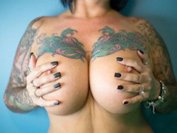 close up of Streamate CatherineTayler's naked tattooed boobs
